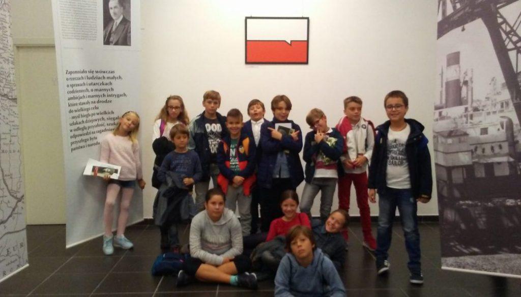 """Uczniowie zwiedzają wystawę """"Młoda grafika dla Niepodległej""""."""